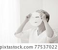 closeup senior asian woman's face and facial mask 77537022