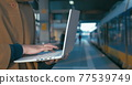 Girl working with laptop at the railway station 77539749