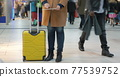 Woman passing time with pad at the airport 77539752