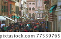 Crowd of people walking along Venetian street 77539765