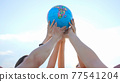 The concept of saving the world. A group of friends raise a world globe in their hands. 77541204