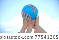 The concept of saving the world. A group of friends raise a world globe in their hands. 77541205