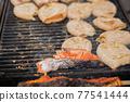 Close up - process of cooking squids and salmon steak on grill - street food 77541444