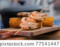 Grilled shrimp, prawn skewer and corn cobs on wooden cutting board - street food 77541447