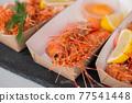 Close up: cooked fresh red langoustine shrimps lemon in paper box - street food 77541448
