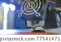 Modern 3D printer machine printing plastic model at exhibition - close up 77541471