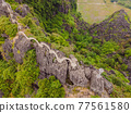 Amazing huge dragon statue at limestone mountain top near Hang Mua view point at foggy morning. Popular tourist attraction at Tam Coc, Ninh Binh. Vietnam travel landscapes and destinations. Vietnam 77561580