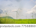 Wind power plant. green meadow with Wind turbines generating electricity 77568860