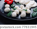 White small mozzarella cheese balls, spinach leaves and tomatoes on black plate. 77631945