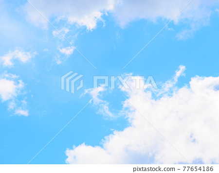 White fluffy clouds floating diagonally in the deep blue sky 77654186