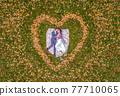 Aerial view of marriage couple lying in a shape of heart made of fall Autumn leafes woods drone photo romantic love 77710065