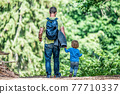 father holding hand of little son with backpack hiking in forest 77710337