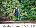 father holding hand of little son with backpack hiking in forest 77710339