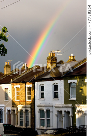 Rainbow emerges with sunlight behind terraced houses after rain 77759254