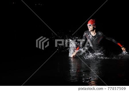 triathlon athlete finishing swimming training at dark night 77857509