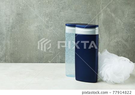 Bottles of shower gel and washcloth against gray background 77914822