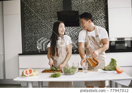 Happy asian couple have fun in modern kitchen indoor 77947812