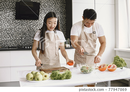 Happy asian couple have fun in modern kitchen indoor 77947869