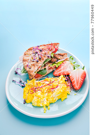 Coarse bread toast with ham, salad and scramble, sprinkled with sprouted seeds. Super food 77960449
