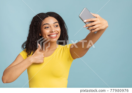 I like it. Happy young black lady taking selfie on smartphone and showing thumb up sign gesture over blue background 77980976