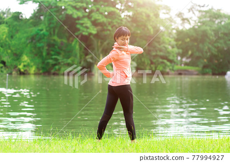 Young female workout before fitness training session at the park. Healthy young woman warming up outdoors. 77994927