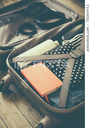 Open suitcase full of clothes isolated on wooden background 78060451