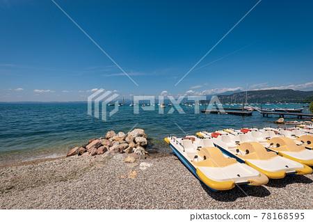 Paddle boats and sailing boats moored on the Lake Garda - Veneto Italy 78168595