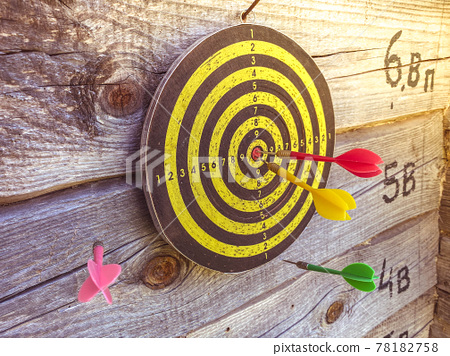 Large playable yellow and black dartboard or darts in the bar against the background of a wooden wall 78182758