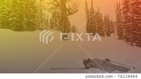 Composition of skier lying in snow in mountains with orange tint 78229984
