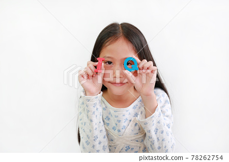 Asian little girl looking through IQ (Intelligence Quotient) sponge text in hands over white 78262754