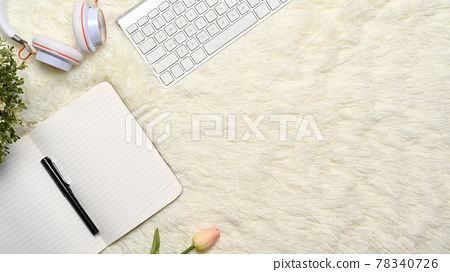 Above view of empty notebook, headphone and keyboard on white rug. 78340726