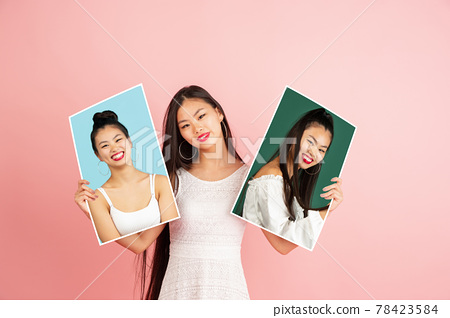Young girl holding her portraits isolated over studio background with copyspace for ad. Concept of beauty, fashion. 78423584