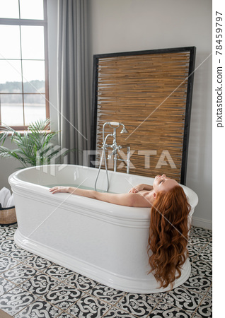 Beautiful ginger woman lying in a bath and looking enjoyed 78459797