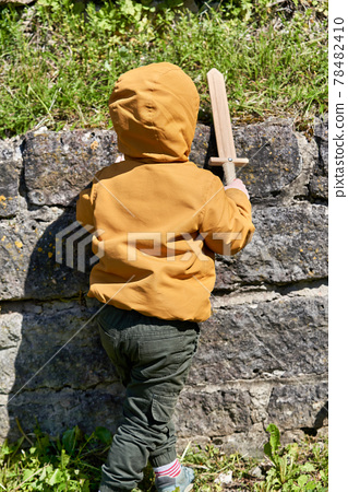 Boy with a toy sword walks on a background of grass 78482410