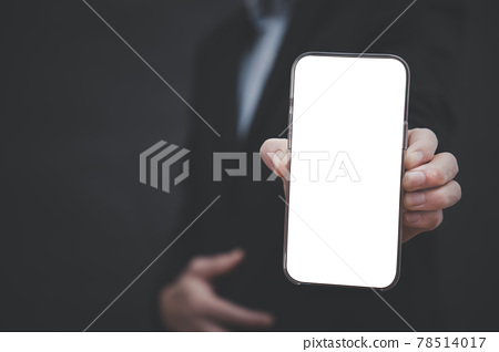 Businessman hand holding mobile white blank screen, Mock up cell mobile smart phone  in suit holds mobile phone with blank white screen on dark blue background,online business concept 78514017