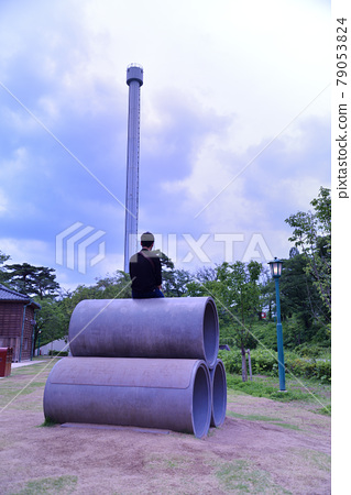 Middle-aged man sitting on a clay pipe and looking at the sky 2 79053824