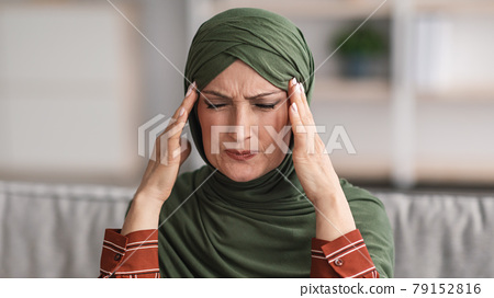 Mature Muslim Woman Suffering From Headache Sitting At Home, Panorama 79152816