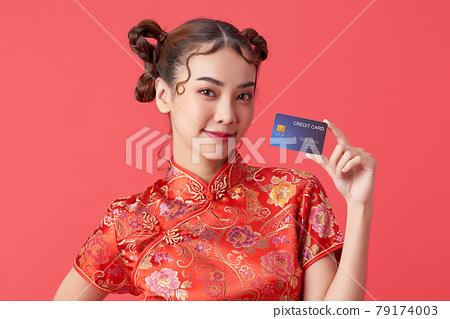 beautiful Asian woman wearing traditional cheongsam qipao dress showing credit card  79174003