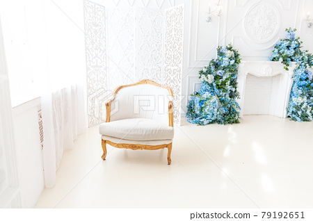 Beautiful luxury classic white bright clean interior bedroom in baroque style with large window, armchair and flower composition. 79192651