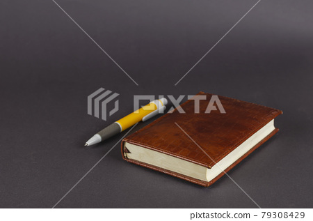 Pen and notebook on a gray background. 79308429