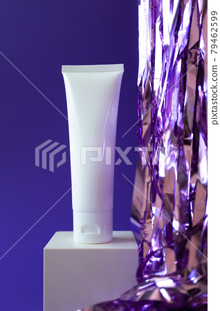 White plastic tube mockup with moisturizer cream, shampoo or facial cleanser and holiday tinsel on cube podium on violet background, vertical 79462599