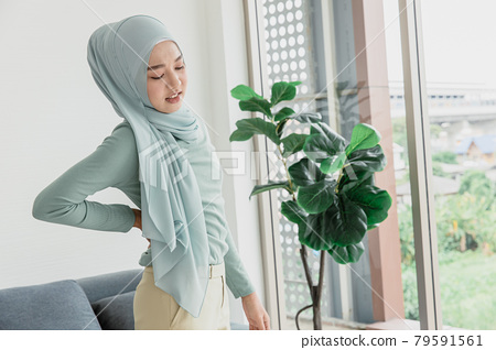 muslim arab women hand at back pain, Waist pain painful expression from office syndrome. 79591561