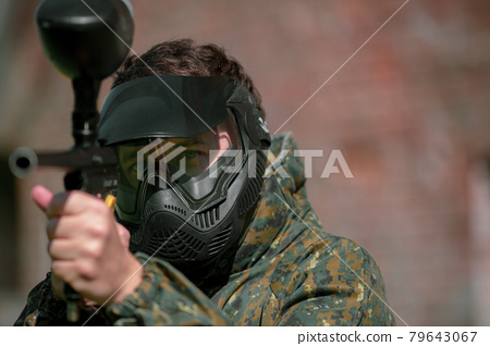 Portrait of young man with face mask and gun in the action game of paintball, simulate military combat using air guns to shoot capsules of paint at each other 79643067