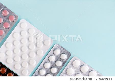 Coronavirus covid-19 outbreak. Tablets in blister, pills, drugs, medicine on blue background.  79664944