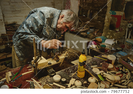 Wood carving artist working on making a model of a wooden toy, a handmade wooden sail ship 79677752