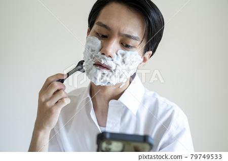 A man shaving his beard 79749533