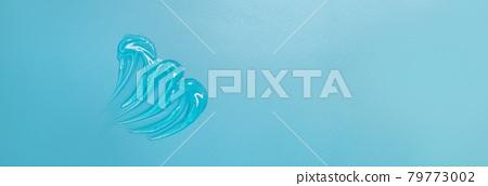 Transparent clear liquid gel cosmetic spot drops texture blue solid color background 79773002