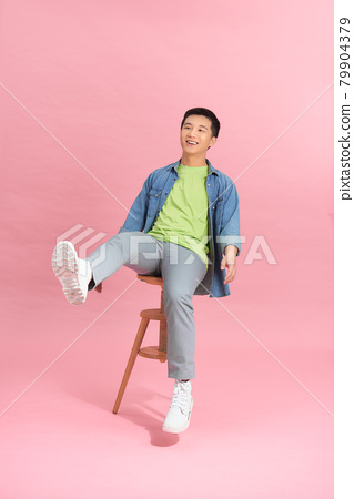 Eager smart casual man looking away sitting on a stool on pink studio background 79904379
