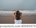 Young woman feeling lonely and sad looking at the sea on a gloomy day 80060979