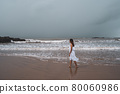Young woman feeling lonely and sad looking at the sea on a gloomy day 80060986